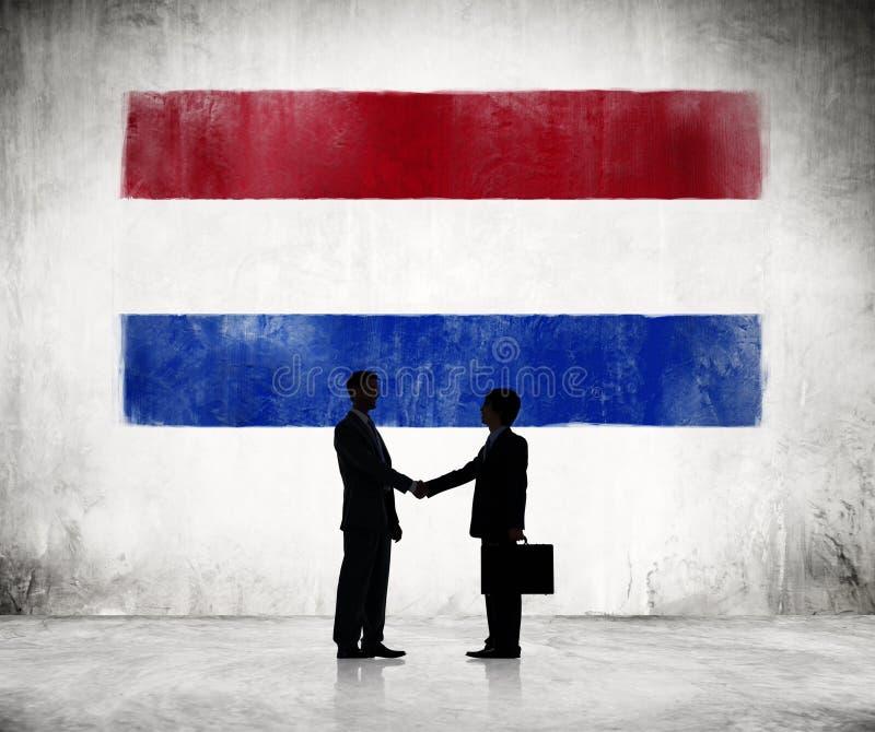Kontur av en affärshandskakning med en holländsk flagga arkivbild