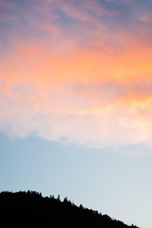 Kontur av en bergkulle mot bakgrunden av aftonhimlen arkivfoto