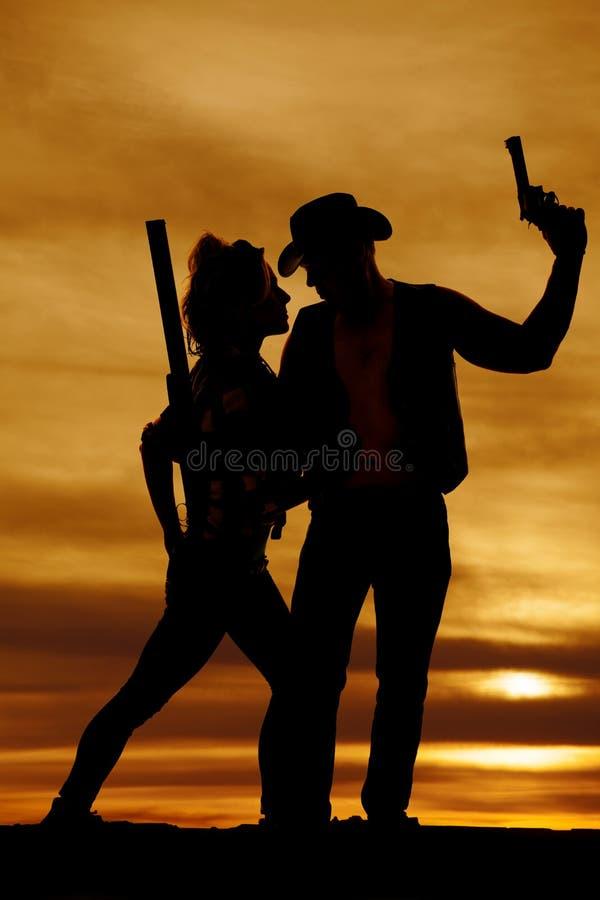 Kontur av en cowgirl och en cowboy tillsammans i solnedgången royaltyfri bild