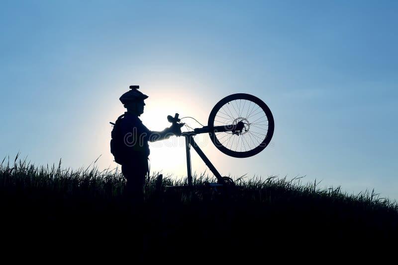 Kontur av en cyklist med en cykel i solen arkivfoto