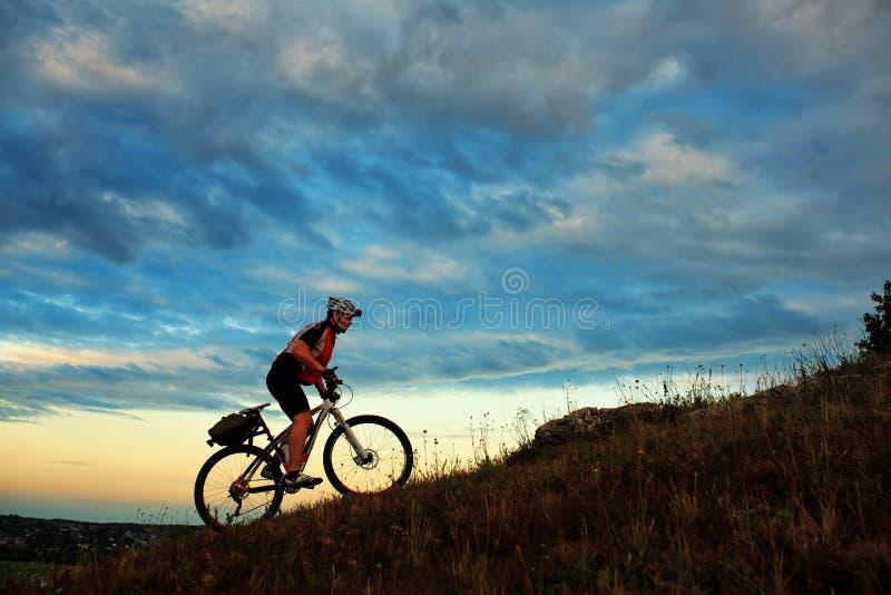 Kontur av en cyklist och en cykel på himmel arkivbilder