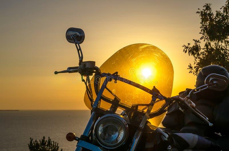 Kontur av en cyklistkvinna som vilar på stranden på solnedgångbakgrund och att tycka om frihet och aktiv livsstil och att ha gyck royaltyfri fotografi