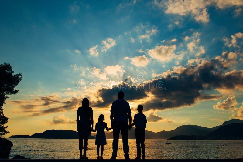 Kontur av en familj med barn mot bakgrunden av det inställningssolen och havet royaltyfri fotografi