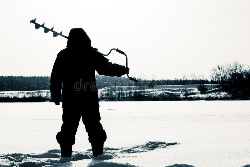 Kontur av en fiskare med en släde lies för fiskeis bara blockerade vinterzander Isfis royaltyfria foton