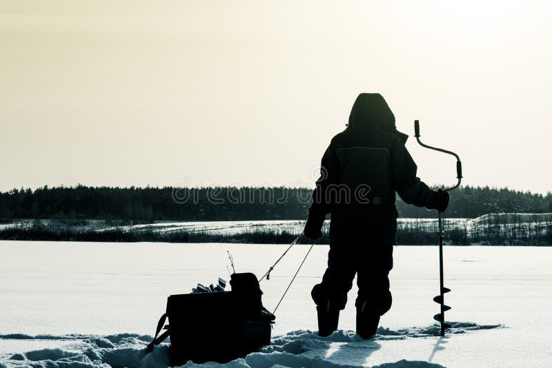 Kontur av en fiskare med en släde lies för fiskeis bara blockerade vinterzander Isfis royaltyfria bilder