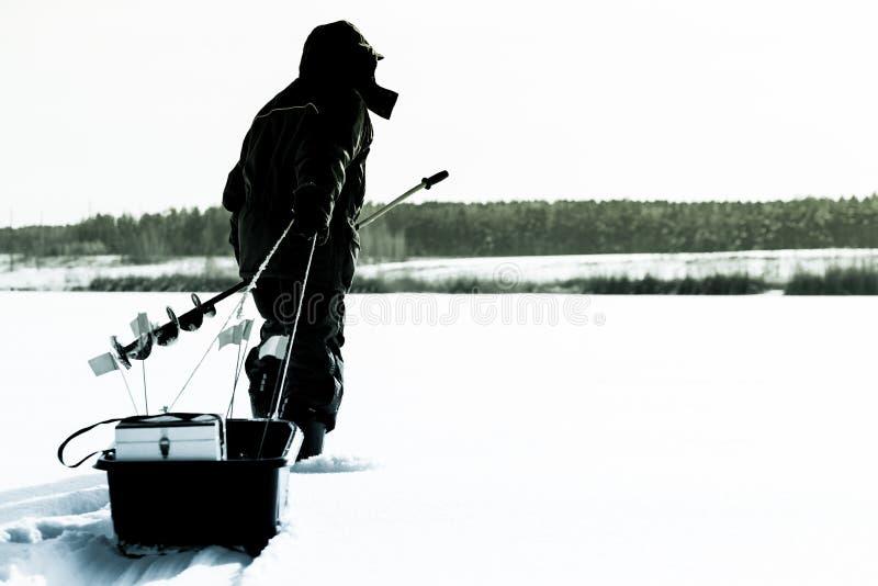 Kontur av en fiskare med en släde lies för fiskeis bara blockerade vinterzander Isfis arkivbild