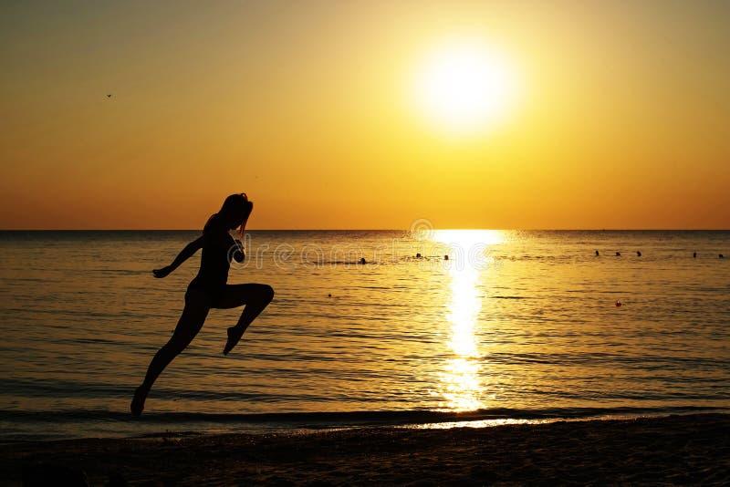 Kontur av en flicka i en baddräkt som kör längs stranden på bakgrunden av gryningen arkivfoto
