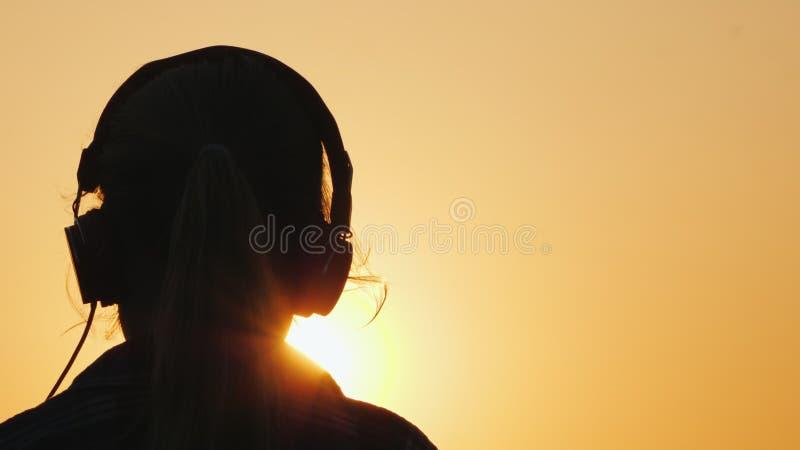 Kontur av en flicka i h?rlurar som lyssnar till musik mot bakgrunden av en stor inst?llningssol och en orange himmel royaltyfri foto