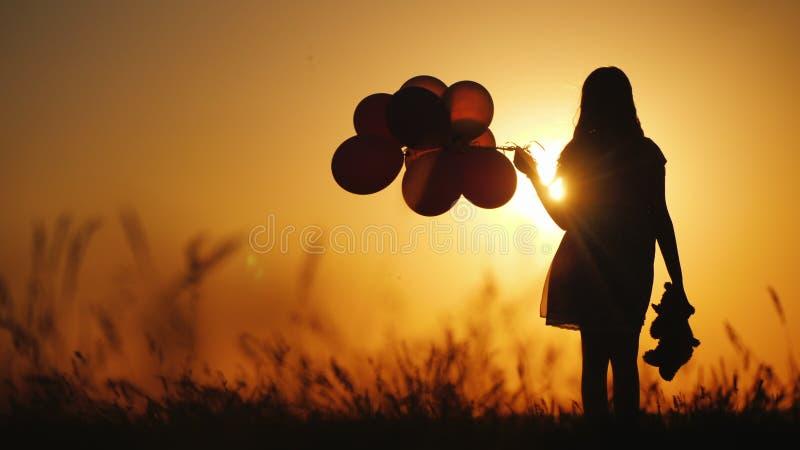 Kontur av en flicka med ballonger och en nallebj?rn Det ?r v?rde solnedg?ngen Avsked till barndombegreppet royaltyfri fotografi