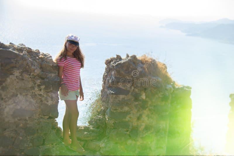 Kontur av en flicka på bakgrunden av havsbakgrunden och stenväggen royaltyfria bilder