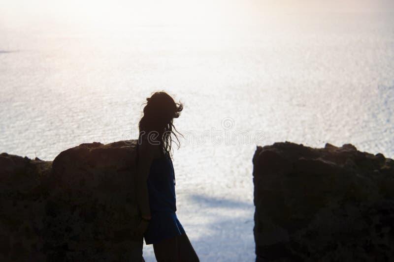Kontur av en flicka på bakgrunden av havsbakgrunden och stenväggen arkivfoton