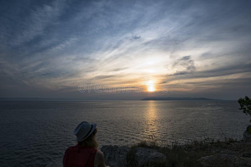 Kontur av en flicka på bakgrunden av solnedgången över Adriatiskt havet arkivfoton