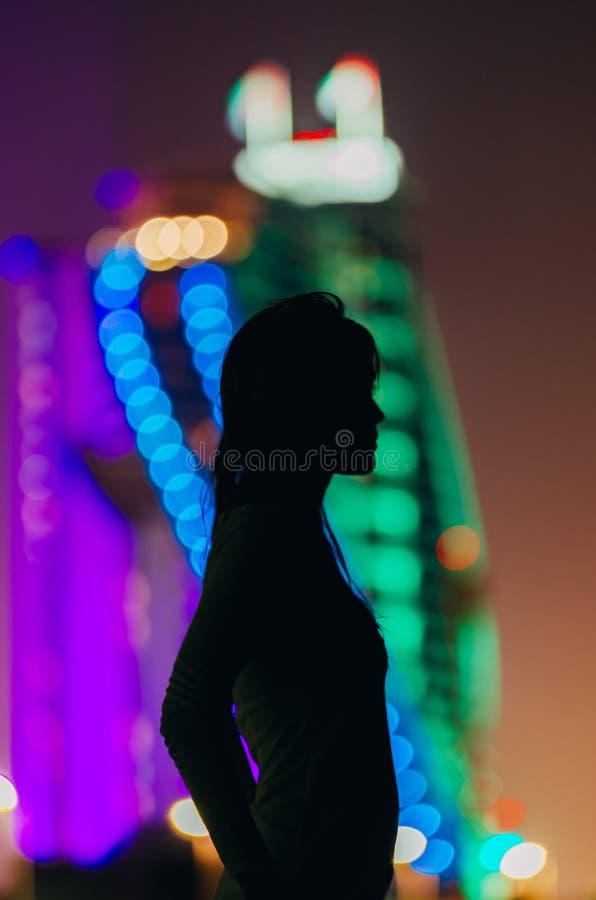 Kontur av en flicka på nattstadsbakgrund med effektbokeh royaltyfri foto