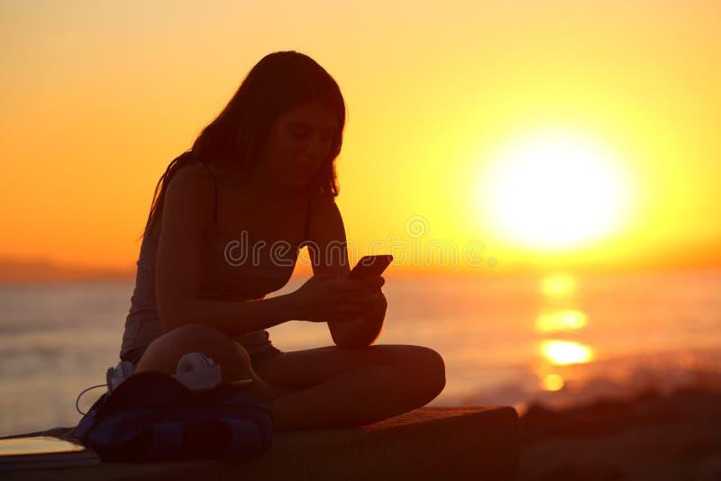 Kontur av en flicka som använder en smart telefon på solnedgången royaltyfri bild