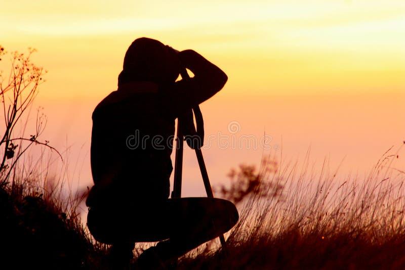 Kontur av en flickafotograf som kopplas in i fotografi från en tripod mot bakgrunden av en orange solnedgång arkivbilder