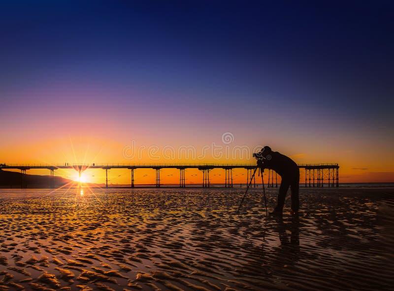 Kontur av en fotograf på härlig solnedgång eller soluppgång på p royaltyfri foto