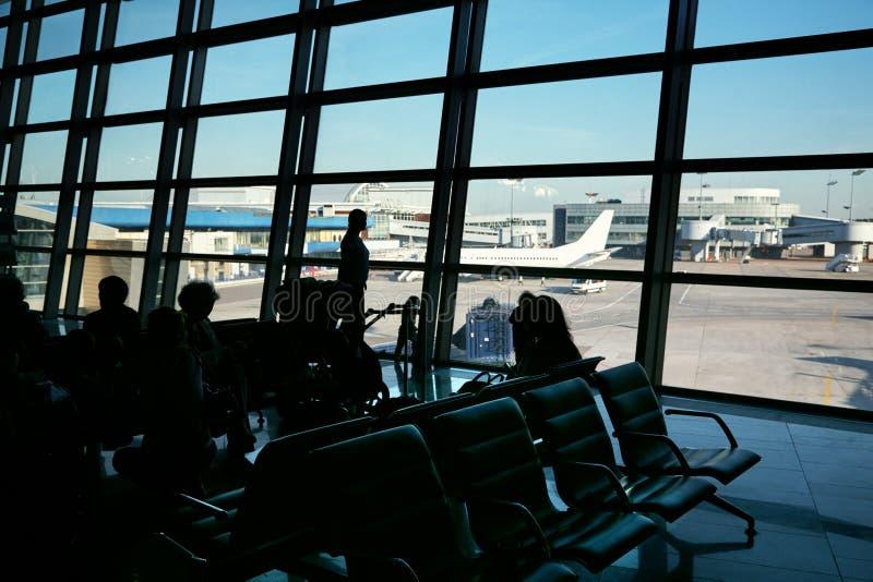 Kontur av en grupp m?nniskor i en v?ntande korridor f?r flygplats royaltyfri foto
