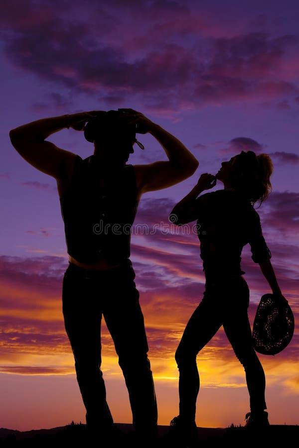 Kontur av en hållande hatt för cowgirl som ser upp på cowboyen royaltyfri foto