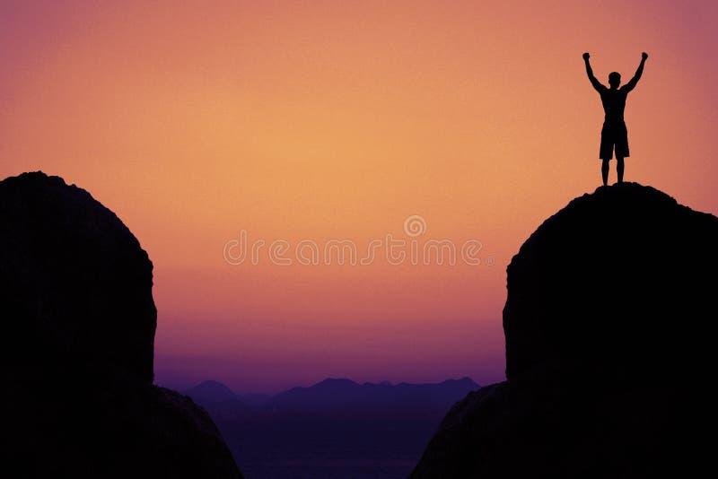 Kontur av en hurra man i berg som symbolet för framgång royaltyfria foton