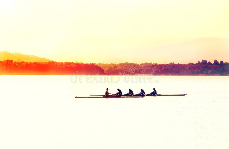 Kontur av en kanot i sjön på solnedgången arkivbild