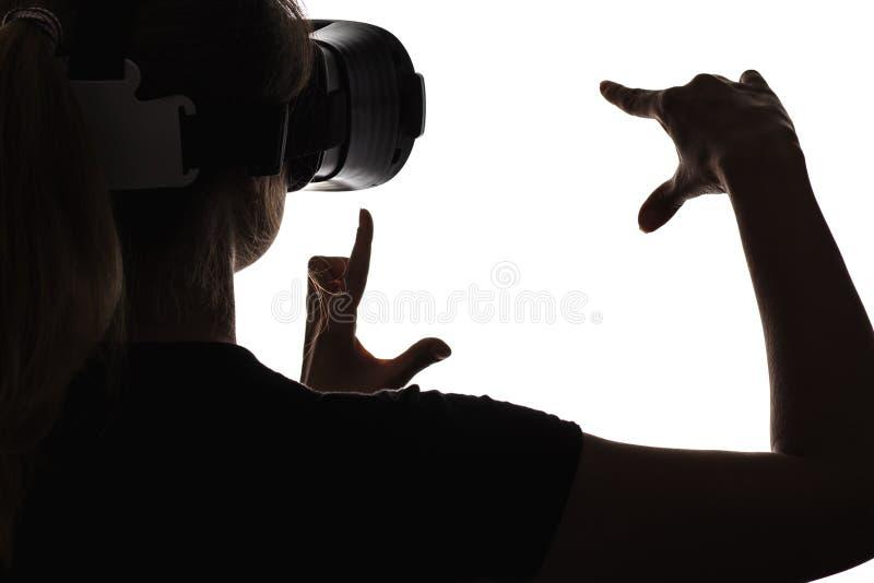 Kontur av en kvinna i anblickar av virtuell verklighet royaltyfri bild