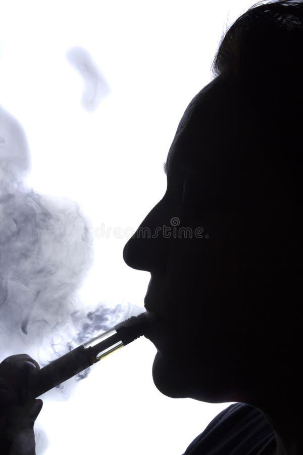 Kontur av en kvinna med en elektronisk cigarett royaltyfri fotografi