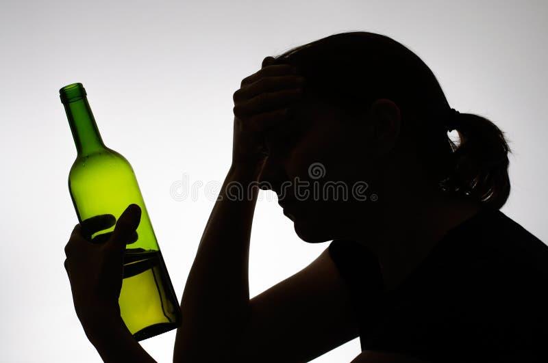 Kontur av en kvinna som rymmer en flaska fotografering för bildbyråer