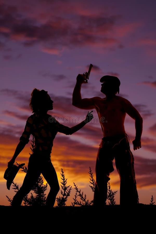 Kontur av en kvinna som rymmer hennes cowboyhatt i en solnedgång med oss arkivbilder
