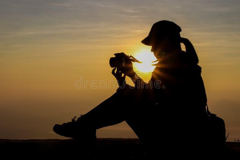 Kontur av en kvinna som rymmer en kamera som tar bilder utanför under soluppgång eller solnedgång royaltyfria bilder