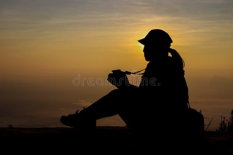 Kontur av en kvinna som rymmer en kamera som tar bilder utanför under soluppgång eller solnedgång royaltyfri fotografi