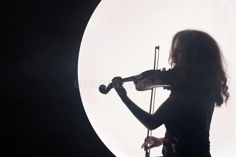 Kontur av en kvinnaviolinist i en vit halvcirkel med rök på en svart bakgrund Ett begrepp för musik under royaltyfri fotografi