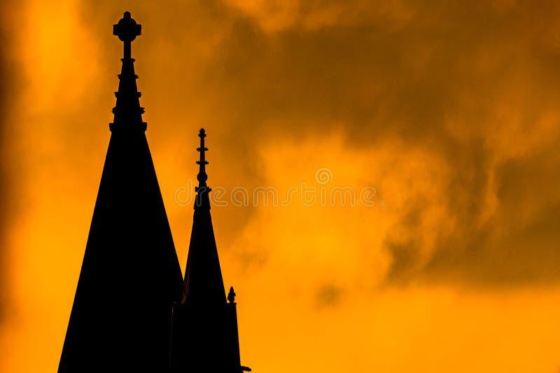 Kontur av en kyrklig kyrktorn, mot ett ljust gult och brännhet-att se himmel under solnedgång, Harlem, New York City, USA royaltyfri fotografi