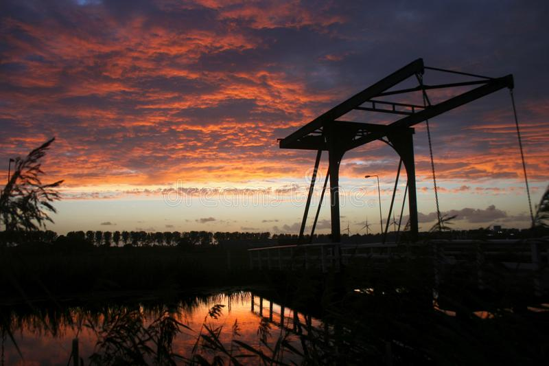 Kontur av en lyftande bro mot en färgrik aftonhimmel royaltyfri bild