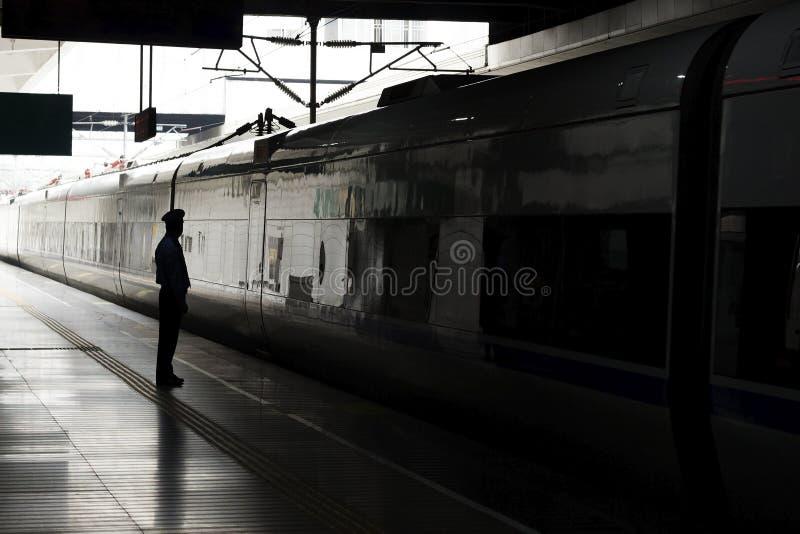 Kontur av en man eller en kvinna på drevstationen i mörkret Begrepp av ensamhet En passagerare som väntar på drevet royaltyfria bilder