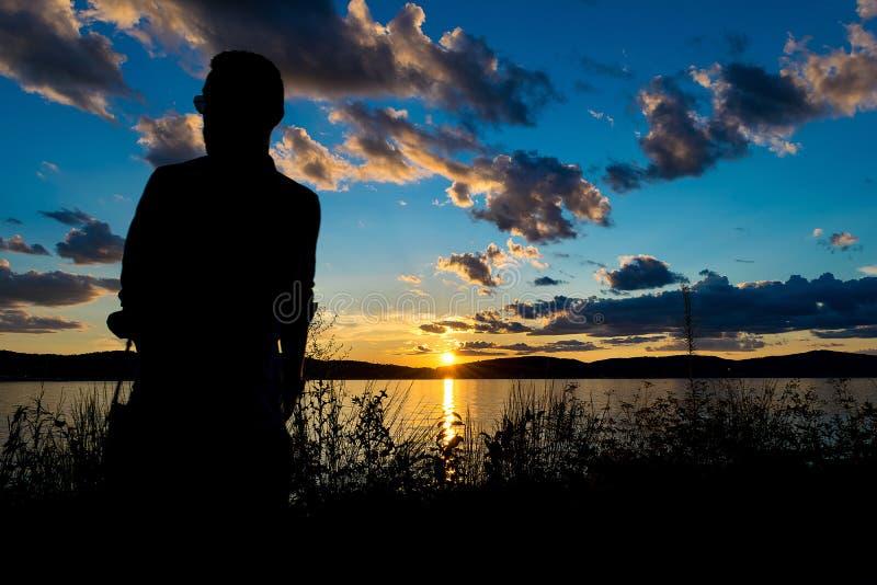 Kontur av en man framme av en dramatisk och härlig solnedgång, vid Hudson River, Upstate New York, NY arkivbild
