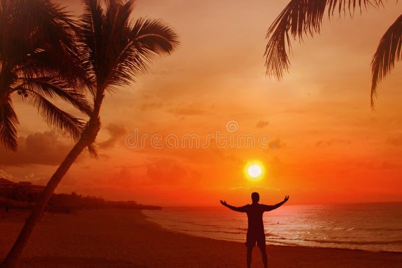 Kontur av en man med hans utsträckta armar Bak honom är en härlig solnedgång över havet, och stranden med gömma i handflatan royaltyfri foto
