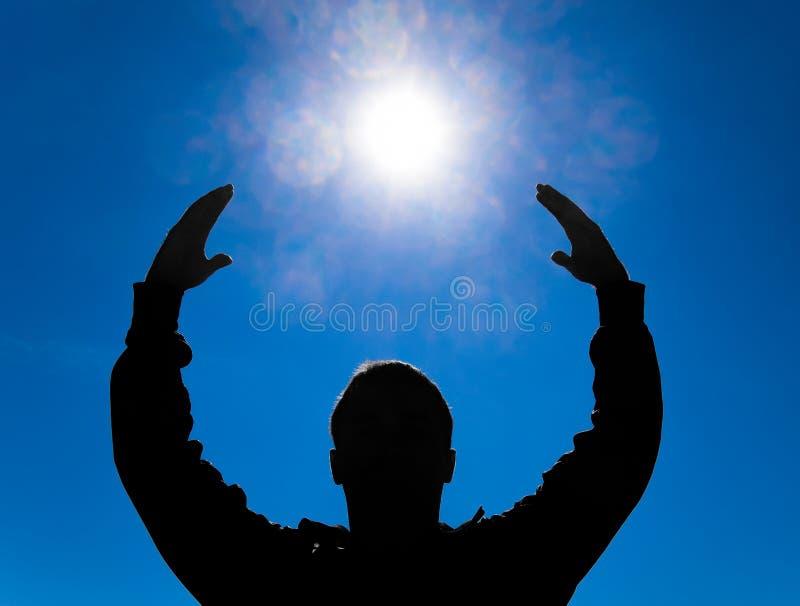 Kontur av en man mot bakgrunden av solen och den blåa himlen Händer lyfts upp till solen royaltyfria bilder