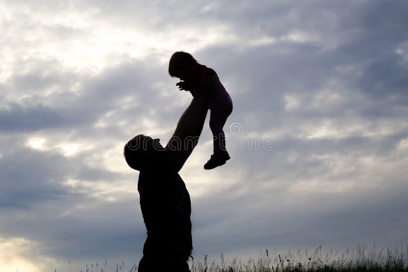 Kontur av en man som bär ett barn fotografering för bildbyråer