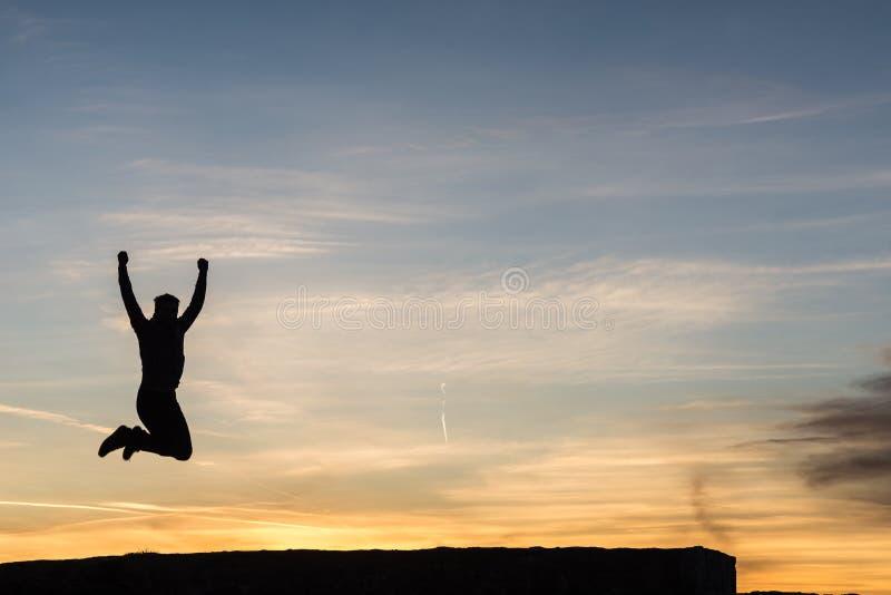Kontur av en man som hoppar högt upp i luften arkivfoto