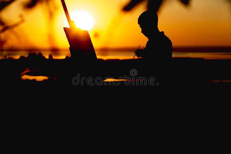 Kontur av en man som målar en bild med målarfärger på kanfas på en staffli på naturen, pojke med målarfärgborsten och paletten so fotografering för bildbyråer