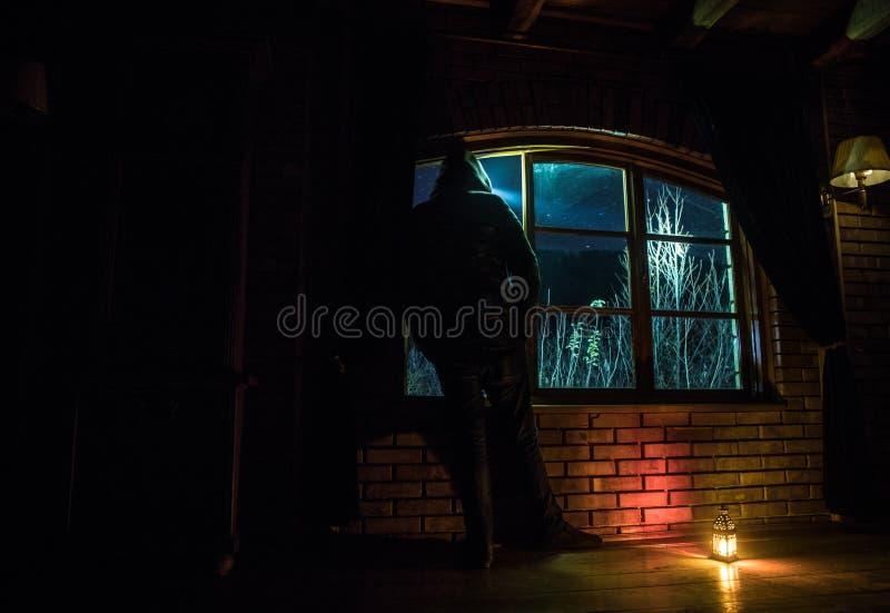 Kontur av en man som ser en drömlik galax till och med ett fönster royaltyfri bild