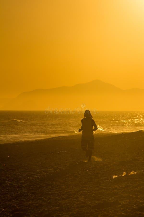 Kontur av en manspring på stranden under solnedgång royaltyfria foton