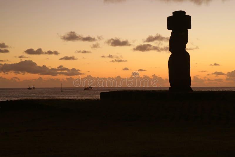 Kontur av en Moai på Ahu Tahai mot solnedgånghimmel och Stilla havet, arkeologisk plats på påskön, Chile arkivfoto