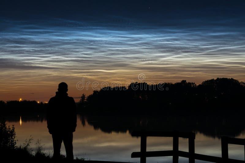 Kontur av en person som ser noctilucent moln NLC, nattmoln nära en sjö i Holland i aftonen arkivfoton