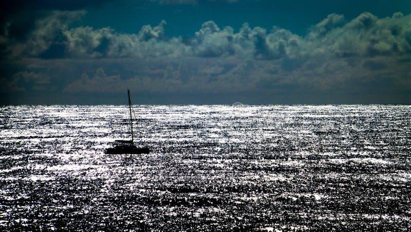 Kontur av en segelbåt på solnedgången med det reflekterande havet royaltyfria bilder