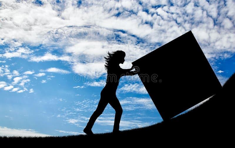 Kontur av en stark kvinna som skjuter en kub till överkanten royaltyfri fotografi