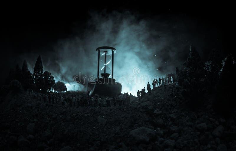 Kontur av en stor folkmassa av folk i skog på nattanseendet mot ett stort timglas med tonade ljusa strålar på dimmig backgrou royaltyfria foton