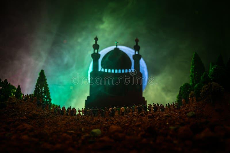 Kontur av en stor folkmassa av folk i skog på nattanseendet mot en suddig moskébyggnad med tonade ljusa strålar på fogg arkivfoto