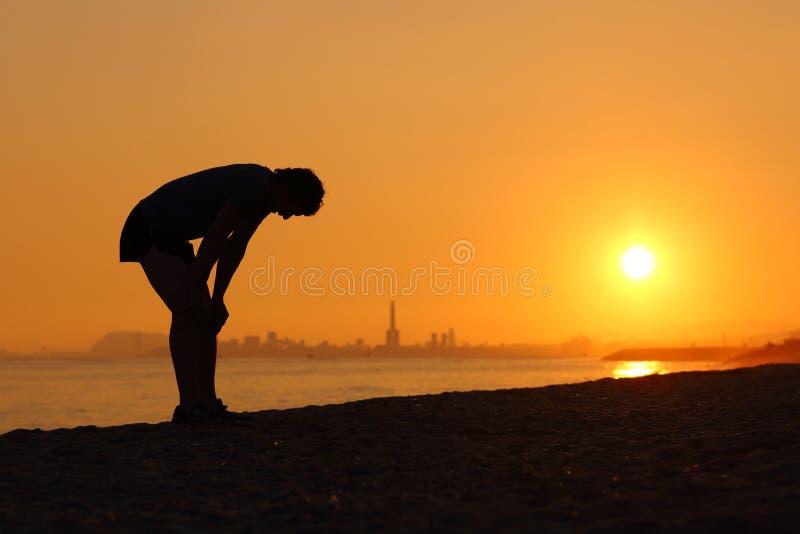 Kontur av en trött idrottsman på solnedgången royaltyfri fotografi