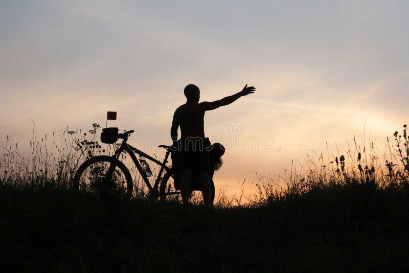Kontur av en turist och en cykel arkivbild
